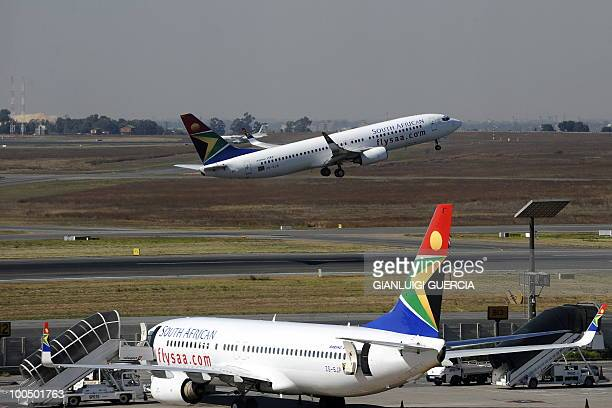 A South African airways flight takes off as another one is parked in a bay on the tarmac on May 25 2010 at the Johannesburg OR Tambo International...