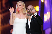 South African and American actress Charlize Theron and French film director Cedric NicolasTroyan wave to fans during The Huntsman Winter's War...