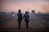 TOPSHOT South African anti riot policemen stand guard a bridge on July 21 2016 as protesters bloc a highway in Meyerton during a service delivery...