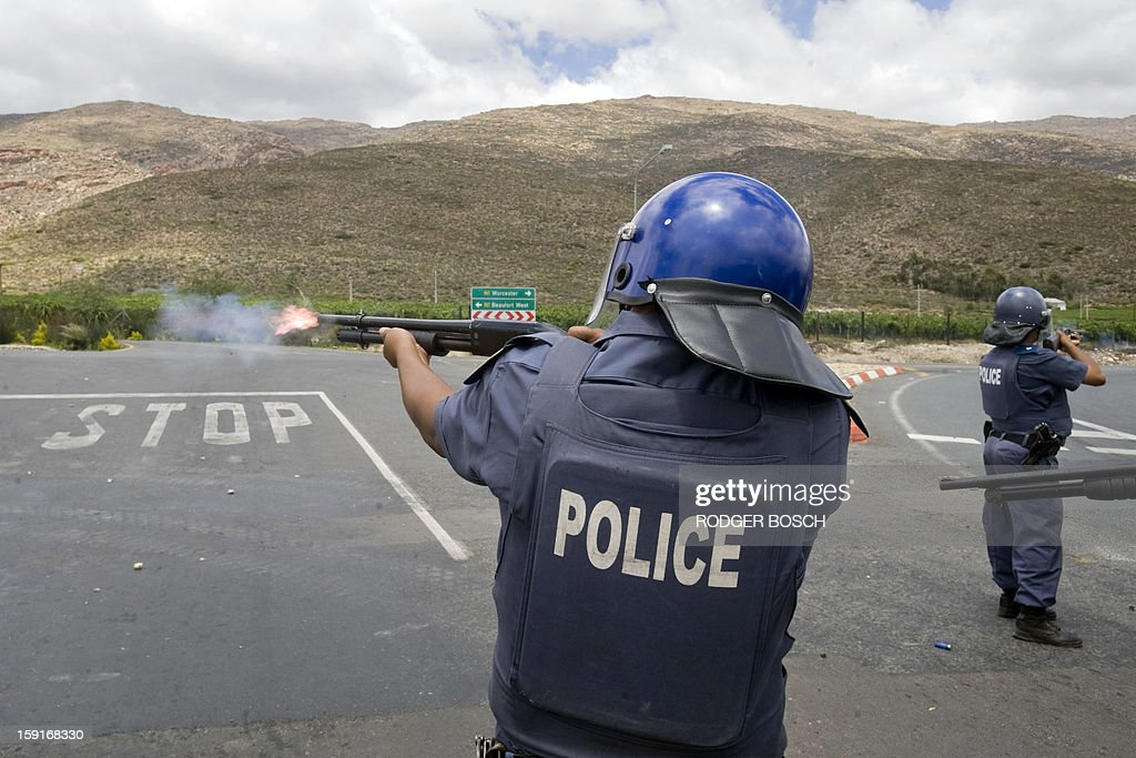 South African anti-riot Police fire rubber bullets at striking farm workers after clashes broke out on January 9, 2013 in De Doorns, a small farming town about 140km north of Cape Town, South Africa. Workers on fruit farms have downed tools, demanding a wage hike from 69 rand ($8) to 150 rand ($17.50) a day. The protesters also occupied part of the country's major N1 highway, forcing dozens of police officers and two armoured vehicles to move down the road, pushing the protesters back from the town entrance. AFP PHOTO / RODGER BOSCH