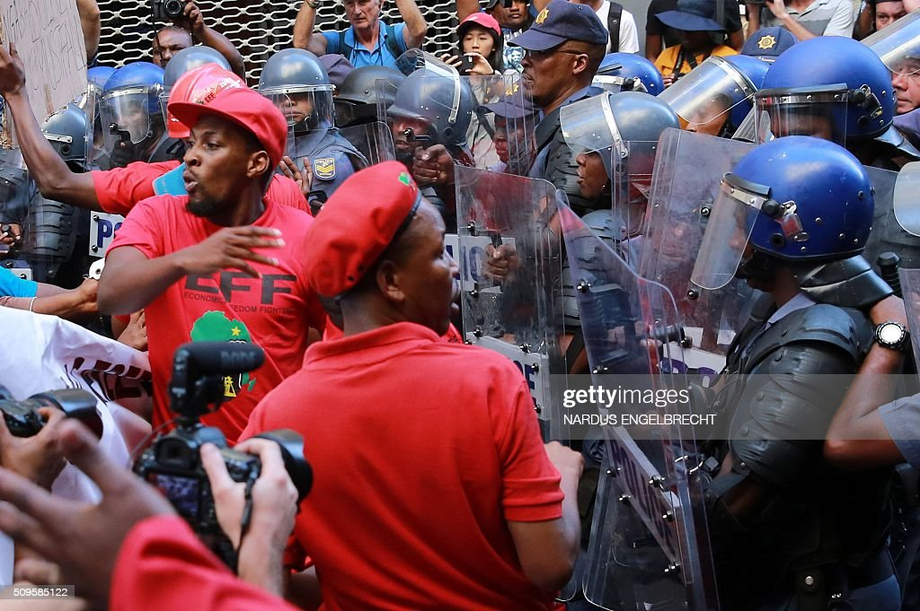 South African anti-riot police officers clash with members of South Africa's radical leftist Economic Freedom Fighters (EFF) party before President Jacob Zuma's state of the nation address on February 11, 2016, in Cape Town. South African police fired stun grenades to disperse angry protesters outside parliament shortly before President Jacob Zuma was due to deliver his annual state of the nation address.The embattled president faces moves in court, in parliament and on the streets to have him impeached or dumped by the ruling African National Congress (ANC). ENGELBRECHT