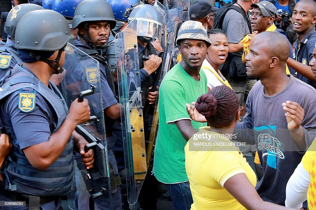 South African anti-riot police officers clash with supporters of South Africa's President Jacob Zuma before his state of the nation address on February 11, 2016, in Cape Town. South African police fired stun grenades to disperse angry protesters outside parliament shortly before President Jacob Zuma was due to deliver his annual state of the nation address.The embattled president faces moves in court, in parliament and on the streets to have him impeached or dumped by the ruling African National Congress (ANC). ENGELBRECHT