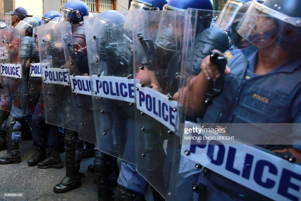 South African anti-riot police officers stand guard during a protest of members of South Africa's radical leftist Economic Freedom Fighters (EFF) party before President Jacob Zuma's state of the nation address on February 11, 2016, in Cape Town. South African police fired stun grenades to disperse angry protesters outside parliament shortly before President Jacob Zuma was due to deliver his annual state of the nation address.The embattled president faces moves in court, in parliament and on the streets to have him impeached or dumped by the ruling African National Congress (ANC). ENGELBRECHT