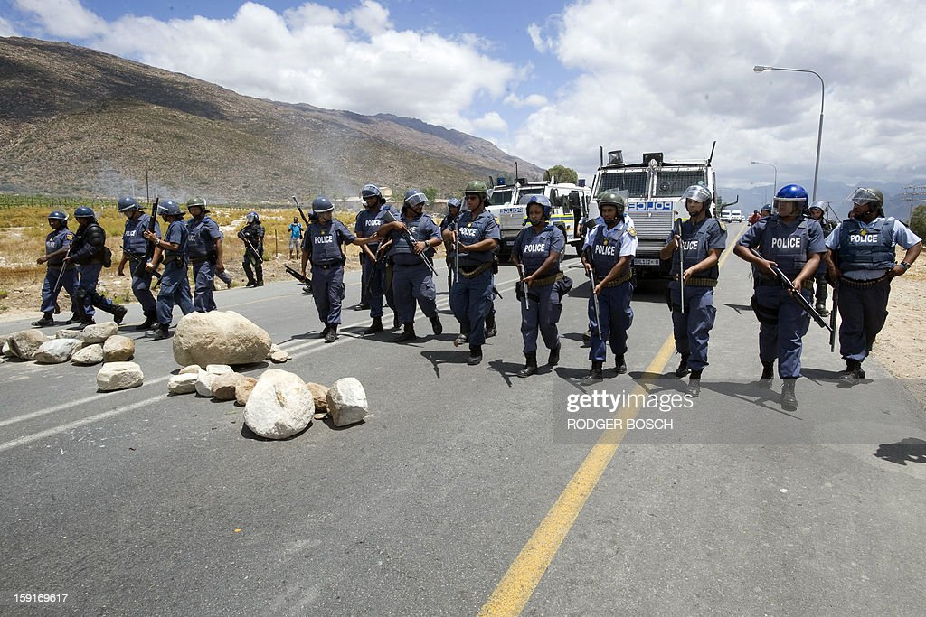 South African anti-riot police officers walk by barricades of rocks set down by striking farm workers after clashes broke out on January 9, 2013 in de Doorns, a small farming town about 140km north of Cape Town, South Africa. Workers on fruit farms have downed tools, demanding a wage hike from 69 rand ($8) to 150 rand ($17.50) a day. The protesters also occupied part of the country's major N1 highway, forcing dozens of police officers and two armoured vehicles to move down the road, pushing the protesters back from the town entrance.