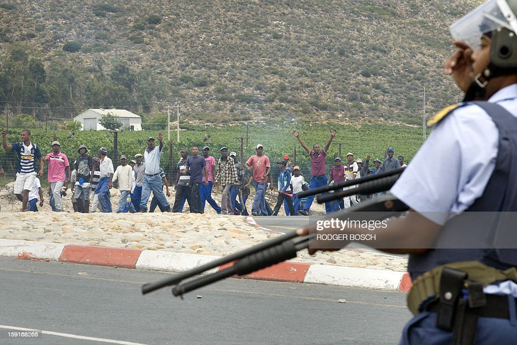 South African anti-riot Police watch striking farm workers after clashes broke out on January 9, 2013 in de Doorns, a small farming town some 140km north of Cape Town, South Africa. Workers on fruit farms have downed tools, demanding a wage hike from 69 rand ($8) to 150 rand ($17.50) a day. The protesters also occupied part of the country's major N1 highway, forcing dozens of police officers and two armoured vehicles to move down the road, pushing the protesters back from the town entrance. AFP PHOTO / RODGER BOSCH