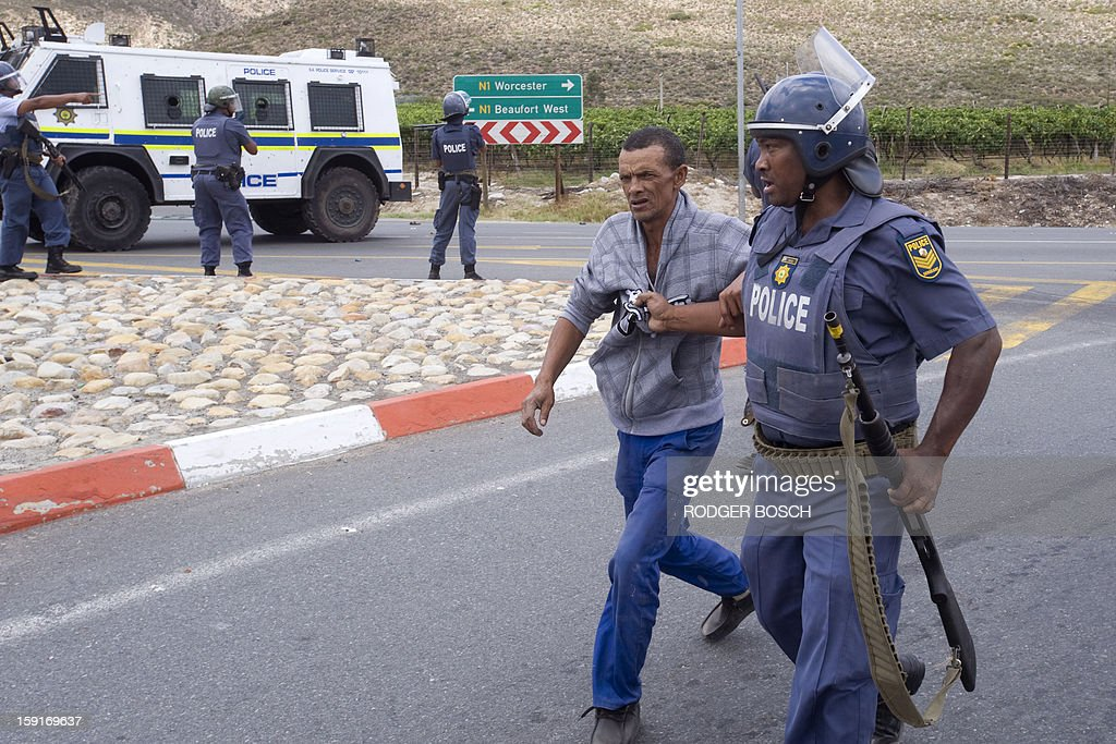 A South African anti-riot Policeman arrests a man during violent clashes with striking farm workers on January 9, 2013 in De Doorns, a small farming town about 140km north of Cape Town, South Africa. Workers on fruit farms have downed tools, demanding a wage hike from 69 rand ($8) to 150 rand ($17.50) a day. The protesters also occupied part of the country's major N1 highway, forcing dozens of police officers and two armoured vehicles to move down the road, pushing the protesters back from the town entrance.