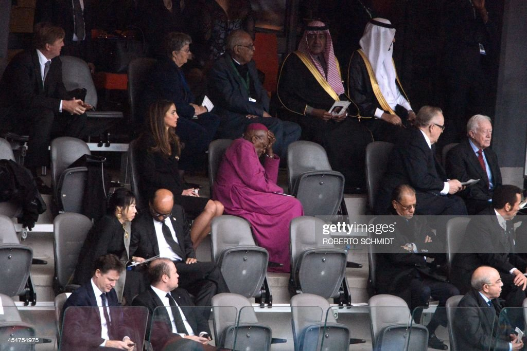 South African Archbishop and Honorary Elders Desmond Tutu (C) and Queen Rania of Jordan attend the memorial service of South African former president Nelson Mandela at the FNB Stadium (Soccer City) in Johannesburg on December 10, 2013. Mandela, the revered icon of the anti-apartheid struggle in South Africa and one of the towering political figures of the 20th century, died in Johannesburg on December 5 at age 95.