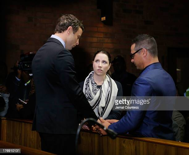 South African athlete Oscar Pistorius prays with his sister Aimee Pistorius and brother Carl Pistorius prior to his indictment hearing in Pretoria...