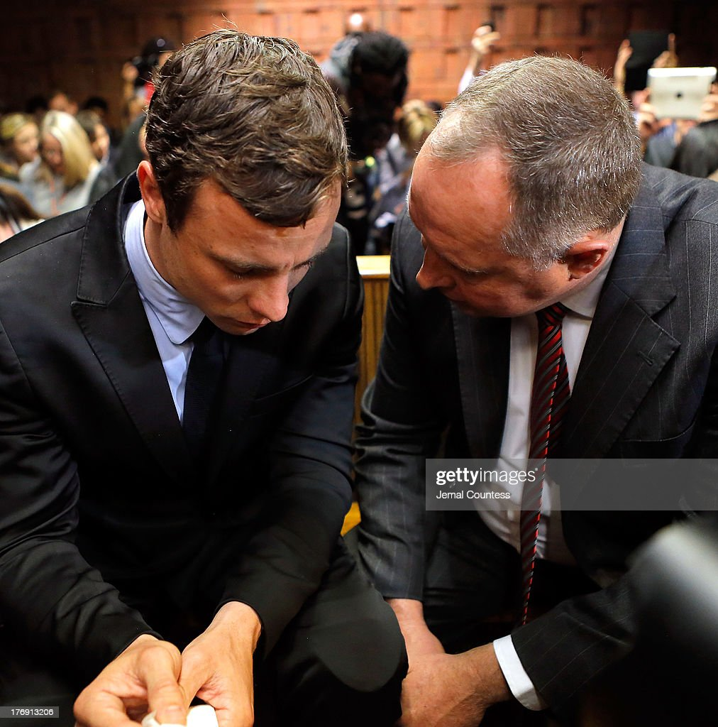 South African athlete Oscar Pistorius speaks with his lawyer Kenny Oldwage in Pretoria Magistrates Court prior to an indictment hearing on August 19...
