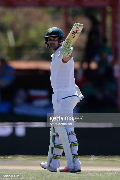 South African batsman Dean Elgar raises his bat to celebrate scoring a half century during the first day of the second cricket Test Match between...