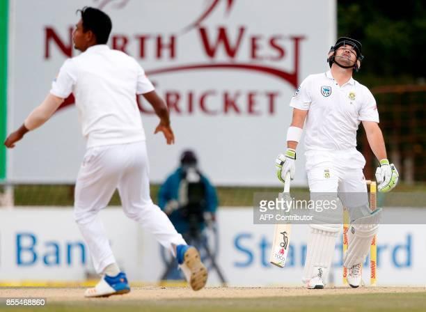 South African batsman Dean Elgar reacts as Bangladesh bowler Mustafizur Rahman celebrates his dismissal during the second day of the first Test...