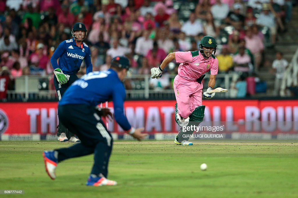 South African batsman Farhaan Behardien (R) plays a shot during the fourth One Day International (ODI) match between England and South Africa at Wanderers on February 12, 2016 in Johannesburg, South Africa. South African players are dressed in pink to raise awareness about breast cancer. / AFP / GIANLUIGI GUERCIA