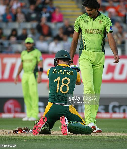 South African batsman Francois Du Plessis and Pakistan bowler Muhammad Irfan look at the demolished wickets after he slides into his crease during...