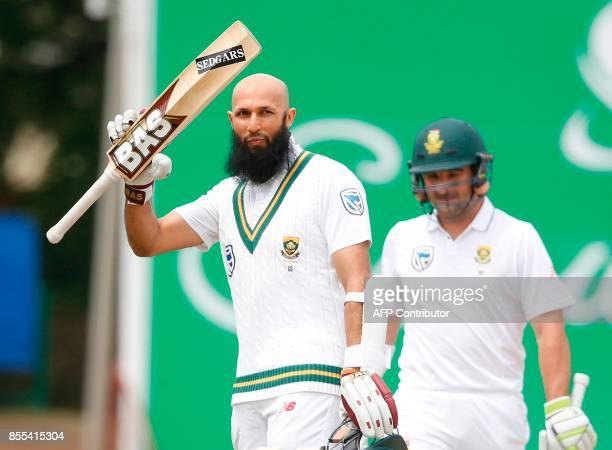 South African batsman Hashim Amla raises his bat after scoring a century during the second day of the first Test cricket match between South Africa...