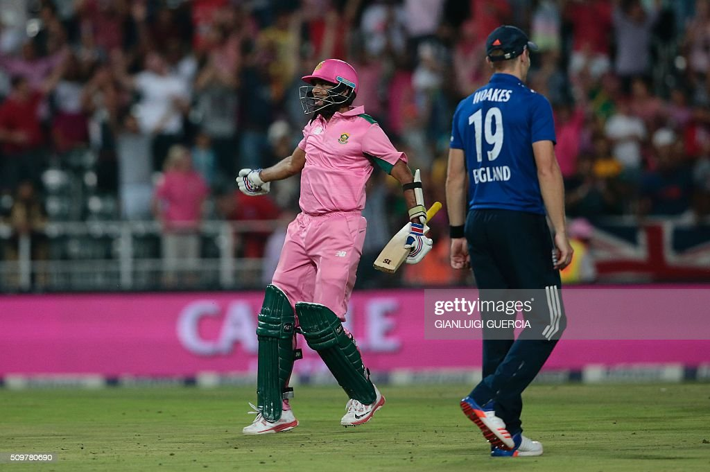 South African batsman Imran Tahir (R) celebrates after South Africa won the fourth One Day International (ODI) cricket match between England and South Africa at Wanderers on February 12, 2016 in Johannesburg, South Africa. South African player are dressed in pink to raise awareness for breast cancer. / AFP / GIANLUIGI GUERCIA