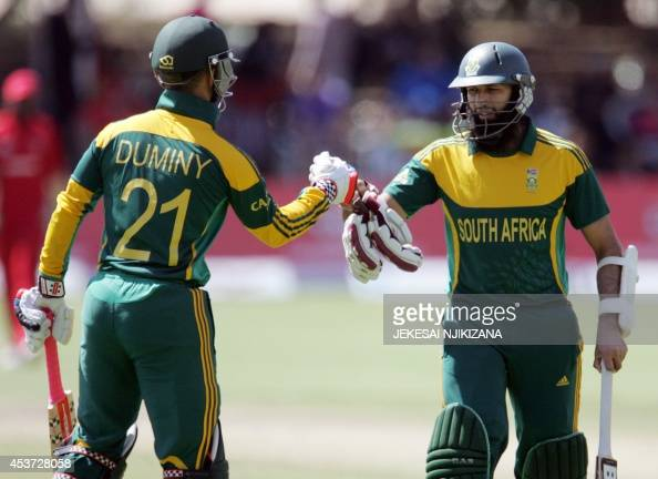 South African batsmen J P Duminy and centurian Hashim Amla leave the pitch at the end of their team's innings during the first cricket match of a...