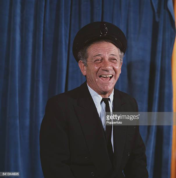 South African born actor Sid James pictured wearing a chauffeur's uniform in character as George Russell from the television sitcom 'George and the...
