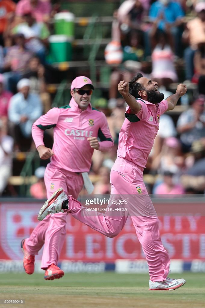 South African bowler Imran Tahir(R) and Captain AB de Villiers(L) celebrate the dismissal of England's batsman Eoin Morgan (not in picture) during the fourth One Day International (ODI) cricket match between England and South Africa at Wanderers on February 12, 2016 in Johannesburg, South Africa. South African players are dressed in pink to raise awareness for breast cancer. / AFP / GIANLUIGI GUERCIA
