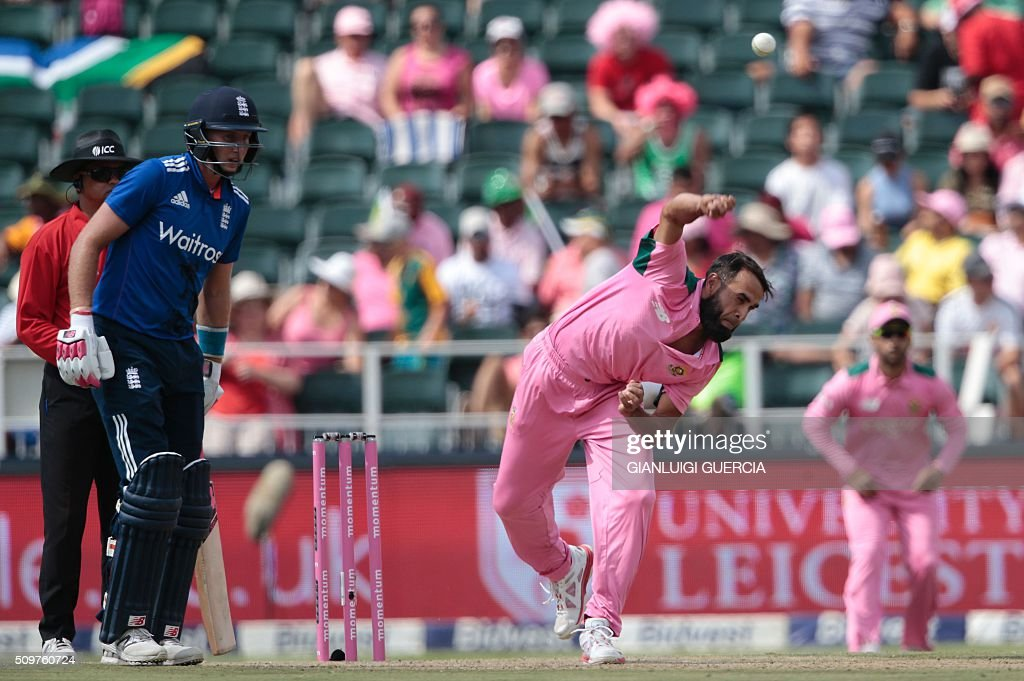 South African bowler Imran Tahir (R) bowls against England's batsman Eoin Morgan (not in picture) during the fourth One Day International (ODI) match between England and South Africa at Wanderers on February 12, 2016 in Johannesburg, South Africa. South African players are dressed in pink to raise awareness about breast cancer. / AFP / GIANLUIGI GUERCIA
