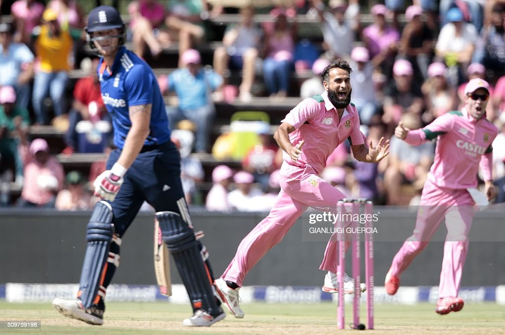 South African bowler Imran Tahir(C) celebrate the dismissal of England's batsman Ben Stokes (L) during the fourth One Day International (ODI) cricket match between England and South Africa at Wanderers on February 12, 2016 in Johannesburg, South Africa. South African players are dressed in pink to raise awareness for breast cancer. / AFP / GIANLUIGI GUERCIA