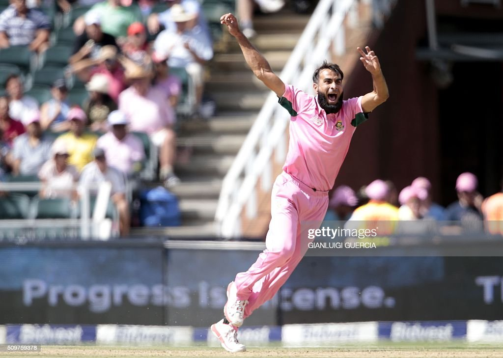 South African bowler Imran Tahir celebrates the dismissal of England's batsman Ben Stokes (Unseen) during the fourth One Day International (ODI) cricket match between England and South Africa at Wanderers on February 12, 2016 in Johannesburg, South Africa. South African players are dressed in pink to raise awareness for breast cancer. / AFP / GIANLUIGI GUERCIA