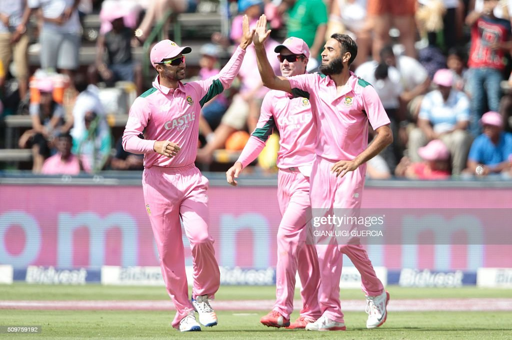 South African bowler Imran Tahir (R) celebrates with teammates the dismissal of England's batsman Eoin Morgan (not in picture) during the fourth One Day International (ODI) cricket match between England and South Africa at Wanderers on February 12, 2016 in Johannesburg, South Africa. South African players are dressed in pink to raise awareness for breast cancer. / AFP / GIANLUIGI GUERCIA