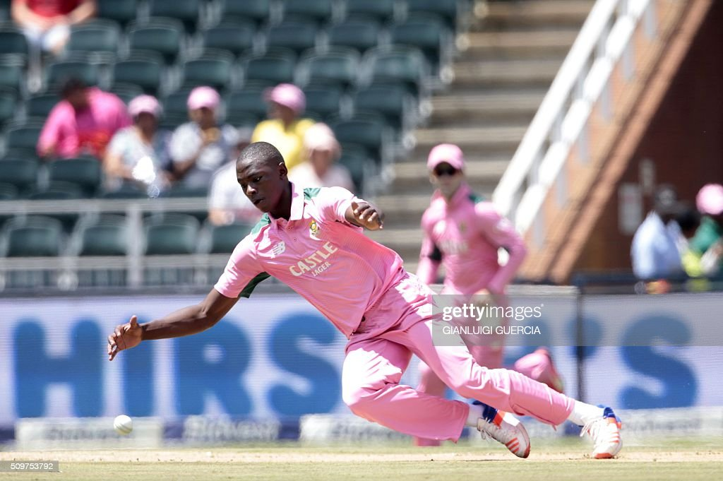 South African bowler Kagiso Rabada attempts to field on his own bowling during the fourth One Day International match between England and South Africa at Wanderers on February 12, 2016 in Johannesburg. South African player are dressed in pink to raise awareness for breast cancer. / AFP / GIANLUIGI GUERCIA