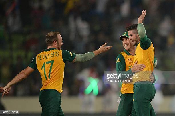 South African bowler Wayne Parnell celebrates the wicket of unseen Indian batsman Ajinkya Rahane with captain Faf du Plessis and teammate AB de...