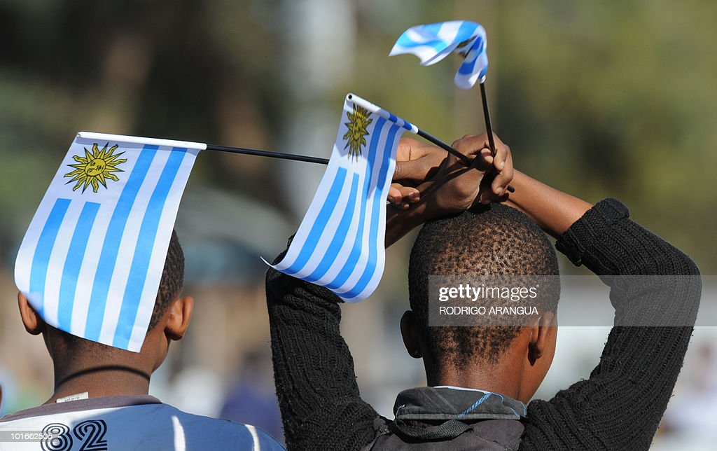 A South African boy holds Uruguayan national flags outside GWK Park stadium in Kimberley before Uruguay's football team's training sesion on June 6, 2010. Uruguay will play their first match of the 2010 World Cup on June 11 in Cape Town. AFP PHOTO / Rodrigo ARANGUA