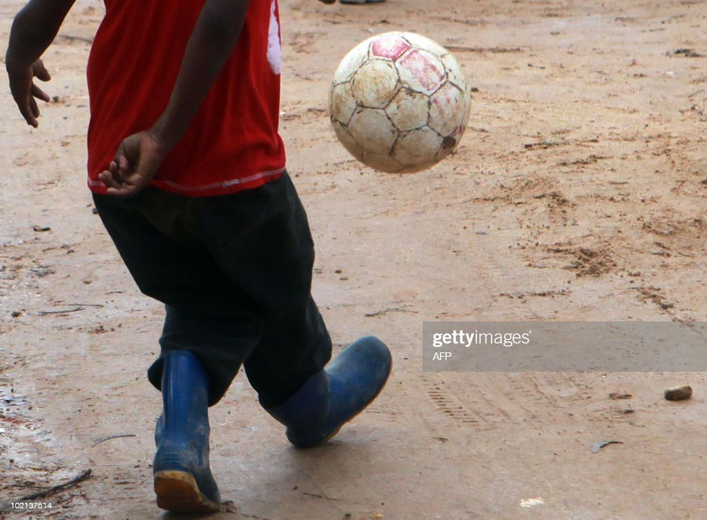 A South African boy plays football on a fruit farm in Stellenbosch, outside Cape Town, on June 16, 2010. South Africa celebrates the 34th anniversary of the Soweto student uprising today. The Bafana Bafana, the South African team, face Uruguay later today in their second match of the 2010 Football World Cup at Loftus in Pretoria. AFP PHOTO / Nardus Engelbrecht