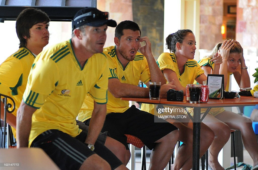 South African captain Graeme Smith (C) and coach Corrie van Zyl (2nd L) watch the South Africa versus Uruguay World Cup football match with family members as they relax before the second test at the Warner Park ground in the St Kitts capital of Basseterre on June 16, 2010. South Africa have taken a 1-0 lead in the three-Test series, with the second test beginning on June 18. AFP PHOTO/Mark RALSTON