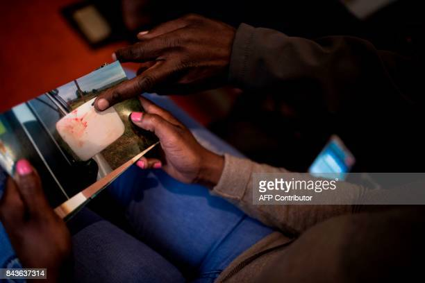 South African chef Nthabiseng Mabuza 35 years old holds a photograph while her husband Rodrique Borge points out the bloodstain on a minibus taxi...