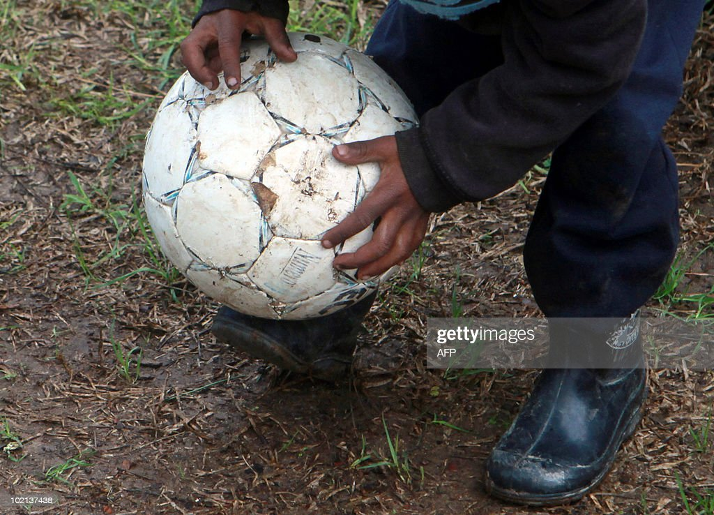 A South African child plays football on a fruit farm in Stellenbosch, outside Cape Town, on June 16, 2010. South Africa celebrates the 34th anniversary of the Soweto student uprising today. The Bafana Bafana, the South African team, face Uruguay later today in their second match of the 2010 Football World Cup at Loftus in Pretoria. AFP PHOTO / Nardus Engelbrecht
