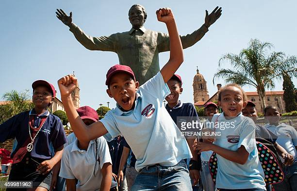 South African children cheer and pose beside the Nelson Mandela statue at the Union Buildings in Pretoria on December 5 2014 South Africans are...