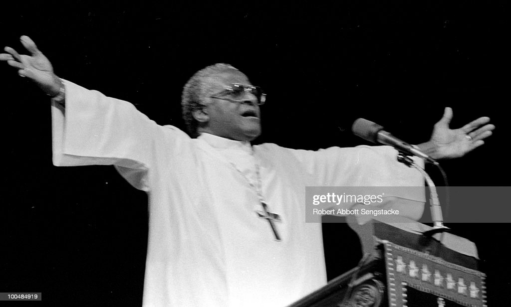 South African cleric Desmond Tutu, the Anglican Archbishop of Cape Town, spreads his arms wide as he addresses the crowd from the lectern of the Cathedral of St. John the Divine, in New York city, 1986.