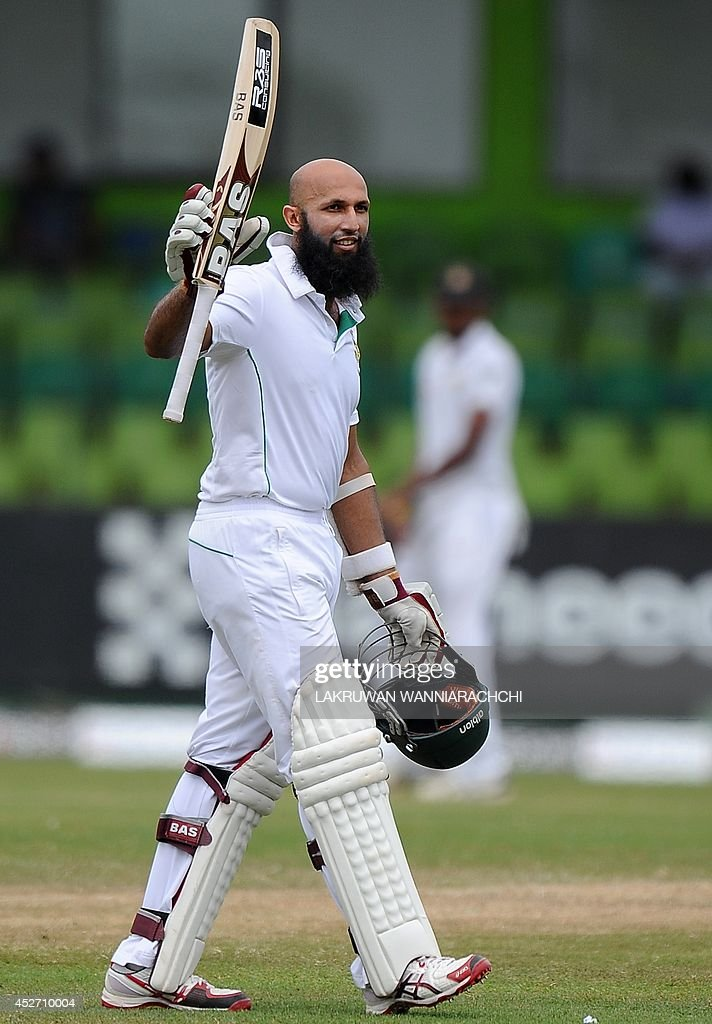 South African cricket captain Hashim Amla raises his bat in celebration after scoring a century (100 runs) during the third day of the second cricket Test match between Sri Lanka and South Africa at the Sinhalese Sports Club (SSC) Ground in Colombo on July 26, 2014.