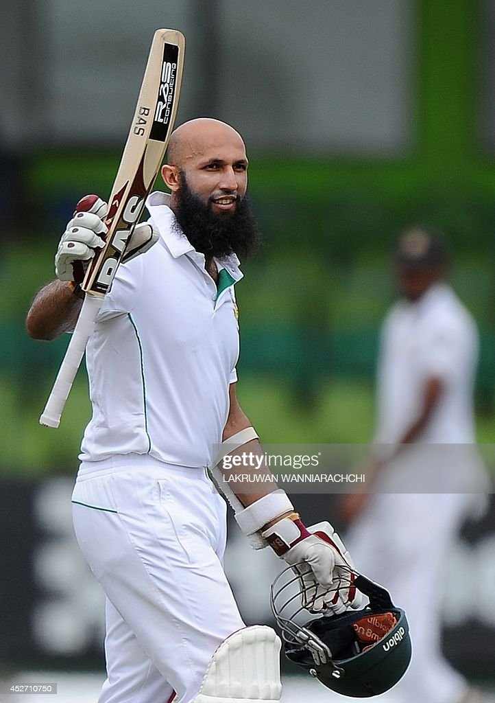 South African cricket captain Hashim Amla raises his bat in celebration after scoring a century (100 runs) during the third day of the second cricket Test match between Sri Lanka and South Africa at the Sinhalese Sports Club (SSC) Ground in Colombo on July 26, 2014. AFP PHOTO/ LAKRUWAN WANNIARACHCHI