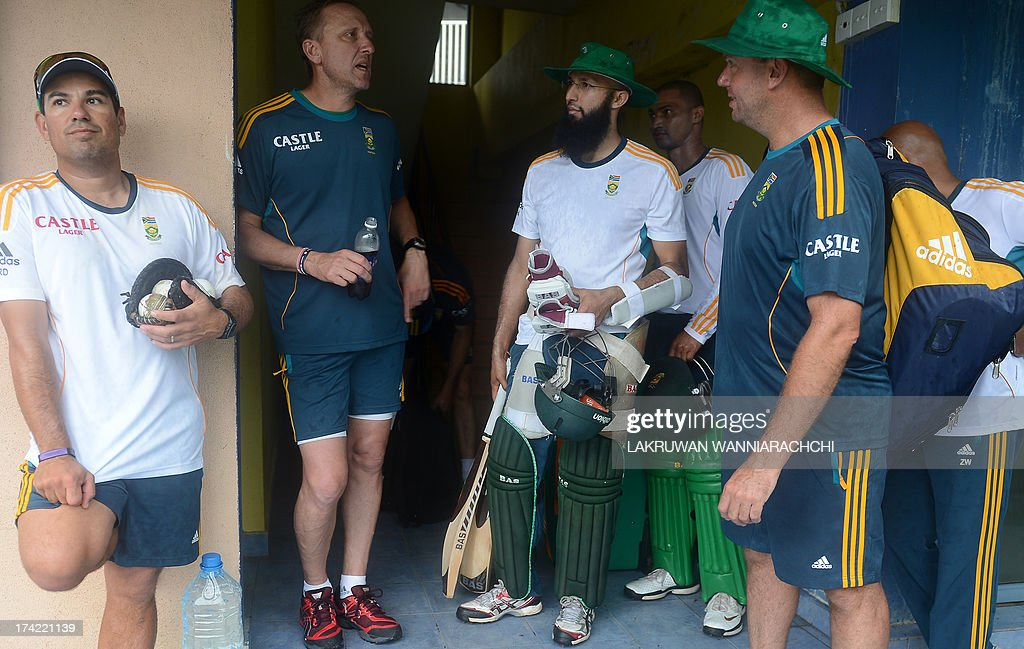 South African cricket coach Russel Domingo (L), bowling coach Allan Donald (2L) cricketers Hashim Amla (C) and Alviro Petersen (3R), and spin bowling coach Claude Henderson (2R) look on after rain stopped play during the practice session at the R. Premadasa Stadium in Colombo on July 22, 2013. Sri Lanka thrashed South Africa by 180 runs in the first one-day international in Colombo with the second match to be played at the same venue on July 23.