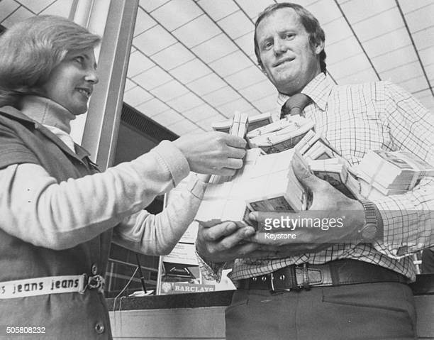 South African cricket player Graeme Pollock holding a huge pile of money after choosing to honor his contract with Australian Kerry Packer and earn...