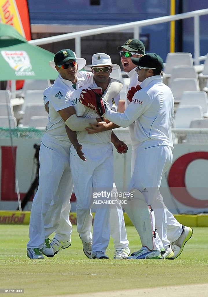 South African cricketer Alviro Petersen (2nd L) is congratulated by teammates for the wicket of unseen Pakistani cricketer Sarfraz Ahmed on day two of the 2nd Test between South Africa and Pakistan, in Cape Town at Newlands on February 15, 2013.