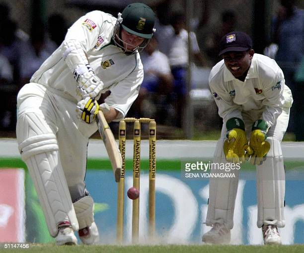 South African cricketer and captain Graeme Smith plays a stroke as Sri Lankan wicketkeeper Romesh Kaluwitharan looks on 06 August 2004 during the...