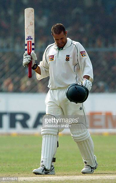 South African cricketer Andrew Hall raises his bat after completing 150 runs on the second day of the first Test match between India and South Africa...