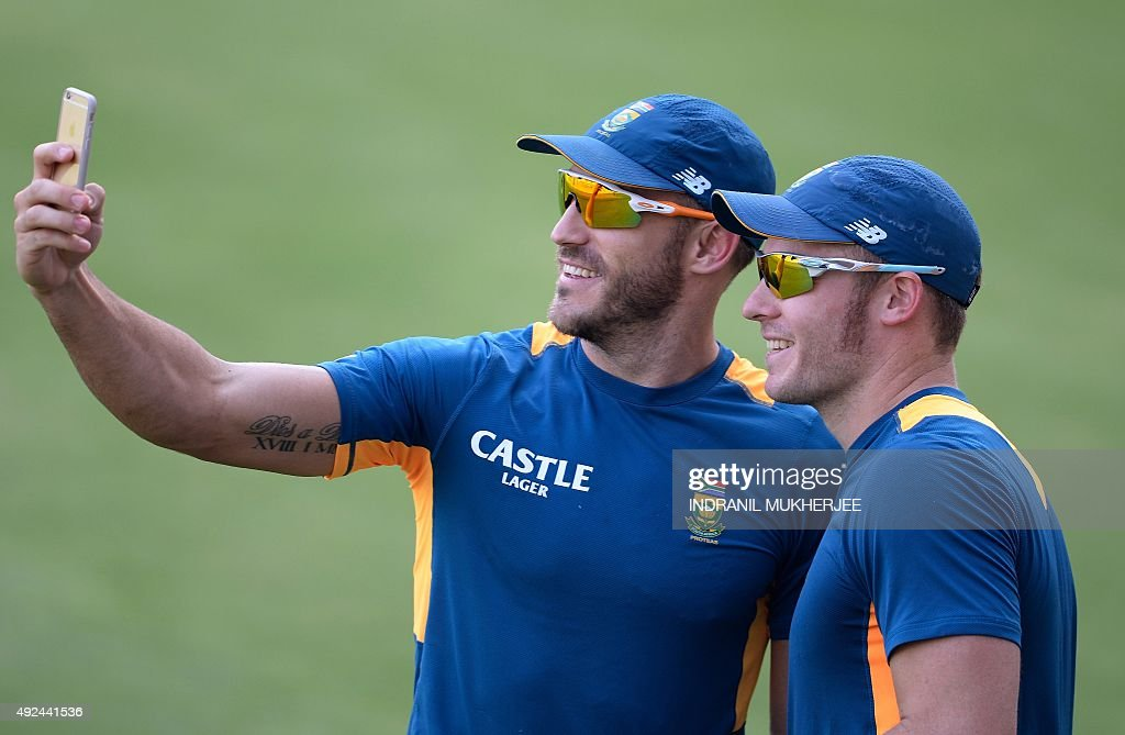 South African cricketer Faf du Plessis (L) takes a velfie, along with teammate <a gi-track='captionPersonalityLinkClicked' href=/galleries/search?phrase=David+Miller+-+Cricket+Player&family=editorial&specificpeople=15061693 ng-click='$event.stopPropagation()'>David Miller</a>, while urging the spectators to cheer during training on the eve of the second one day international (ODI) cricket match between India and South Africa at The Holkar Cricket Stadium at Indore on October 13, 2015.