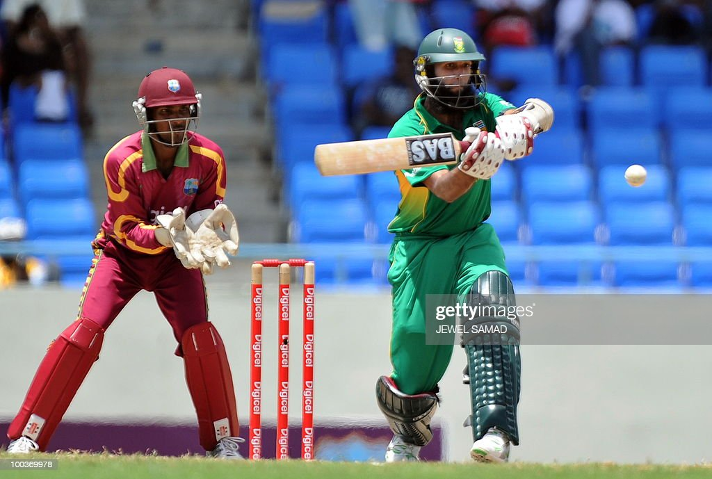 South African cricketer Hashim Amla hits the ball as West Indies wicketkeeper Denesh Ramdin looks on during the second One Day International match between West Indies and South Africa at the Sir Vivian Richards Stadium in St John's on May 24, 2010. AFP PHOTO/Jewel Samad