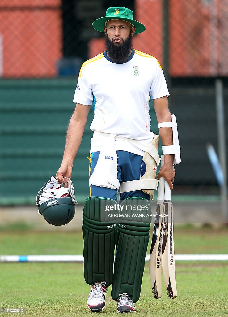 South African cricketer Hashim Amla walks with his equipment during a practice session at the R. Premadasa Stadium in Colombo on July 22, 2013.The second ODI between South Africa and Sri Lanka will be played on July 23, 2013.
