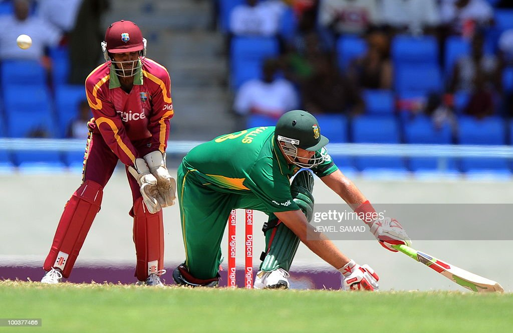 South African cricketer Jacques Kallis plays a shot as West Indies wicketkeeper Denesh Ramdin looks on during the second One Day International match between West Indies and South Africa at the Sir Vivian Richards Stadium in St John's on May 24, 2010. AFP PHOTO/Jewel Samad