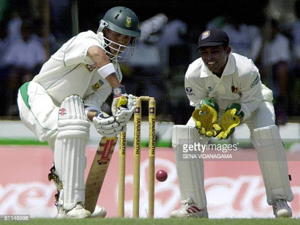 South African cricketer Jacques Rudolph plays a stroke as Sri Lankan wicketkeeper Romesh Kaluwitharana looks on during the third day of the first...