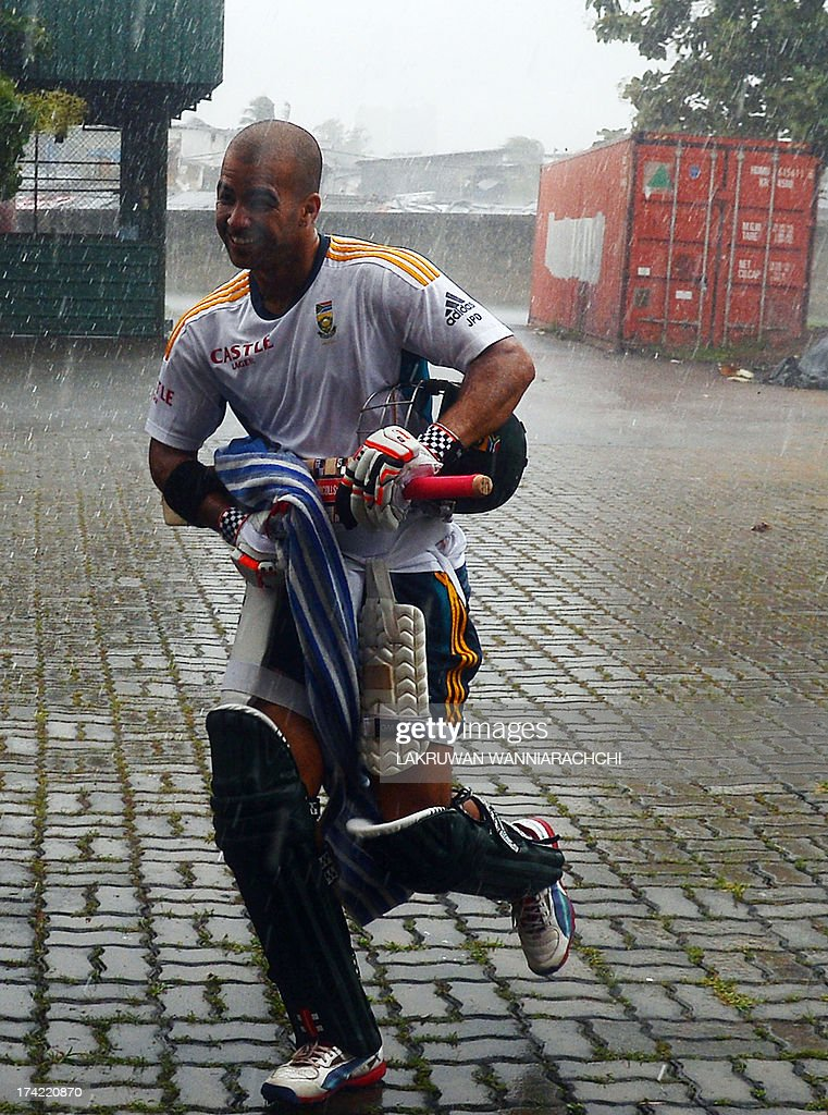 South African cricketer Jean-Paul Duminy runs in the rain prior to the start of the practice session at the R. Premadasa Stadium in Colombo on July 22, 2013.The second ODI between South Africa and Sri Lanka will be played on July 23, 2013.
