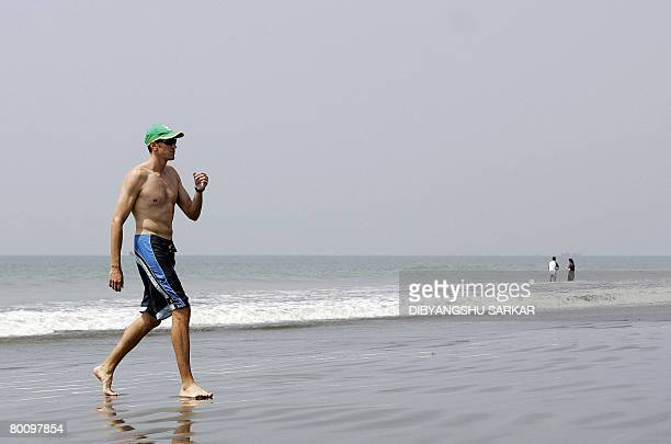 South African cricketer Morne Morkel walks on the beach as security officers stand guard at Cox's Bazaar on March 4 2008 Some members of the South...