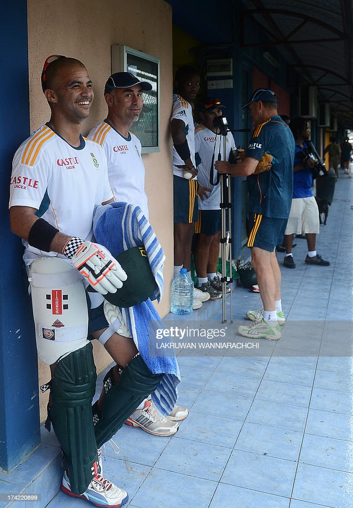 South African cricketer's Jean-Paul Duminy (L) and teammates look on after rain prior to the start of a practice session at the R. Premadasa Stadium in Colombo on July 22, 2013.The second ODI between South Africa and Sri Lanka will be played on July 23, 2013.